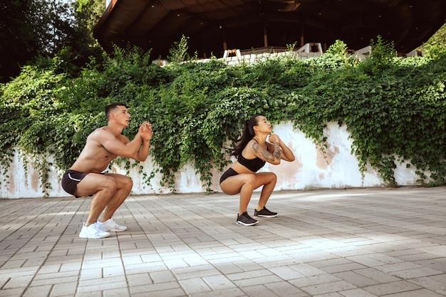 公園で運動をしている筋肉の運動選手。体操、トレーニング、フィットネストレーニングの柔軟性。