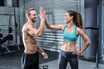 A muscular couple clapping hands