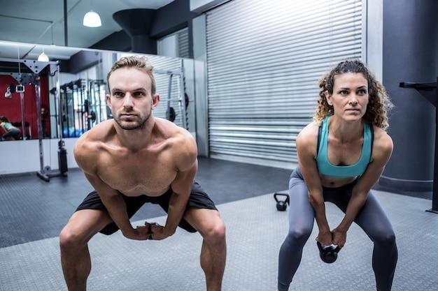 筋肉のカップルケトルベルを持ち上げる