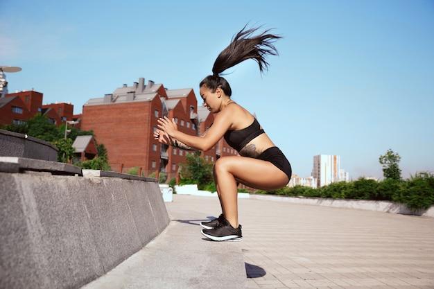 公園で運動をしている筋肉質の女性アスリート。体操、トレーニング、フィットネストレーニングの柔軟性。背景フィールドの晴れた日の夏の街。アクティブで健康的なライフスタイル、若者、ボディービル。