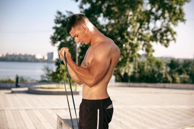 Мускулистый спортсмен-мужчина делает тренировку в парке. гимнастика, тренировки, гибкость фитнес-тренировок.