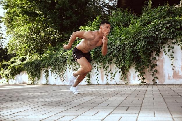 公園でトレーニングをしている筋肉質の男性アスリート