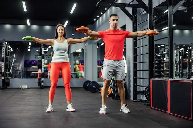 근육질의 남자와 밤 시간에 실내 체육관에서 함께 팔과 어깨 운동을하는 아름다운 젊은 여자
