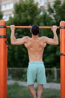 筋肉質の男がスポーツフィールドの路上で鉄棒を引き上げる