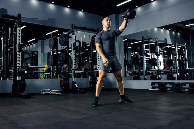 灰色のtシャツを着た筋肉質の男性が、照明の少ないジムでクロスフィットトレーニングを行っています