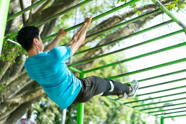 体操服を着た筋肉質の男性が、公園での登山に最適な懸垂をしている。