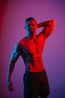 あごひげを生やした筋肉質の男性が青と赤の光の下で頭の後ろに腕を持ってポーズをとっている