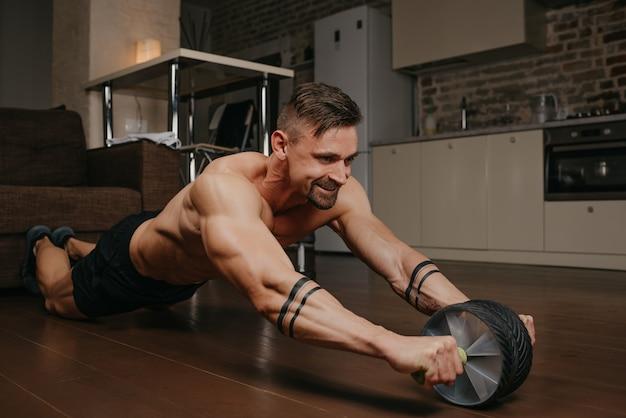 알몸의 몸통을 가진 근육질의 남자가 저녁에 아파트에서 복근 운동을하고 있습니다.