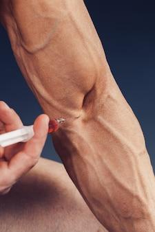 注射器を持った筋肉質の男