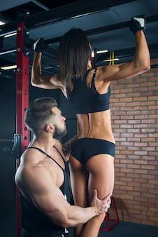 筋肉の細切り男がスポーティな女の子がジムの鉄棒でプルアップをするのを手伝っています