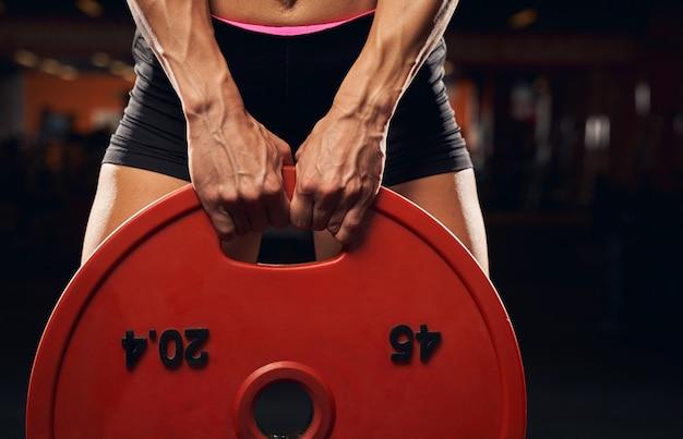 Мускулистая женщина, использующая круглые гантели для тренировки в тренажерном зале