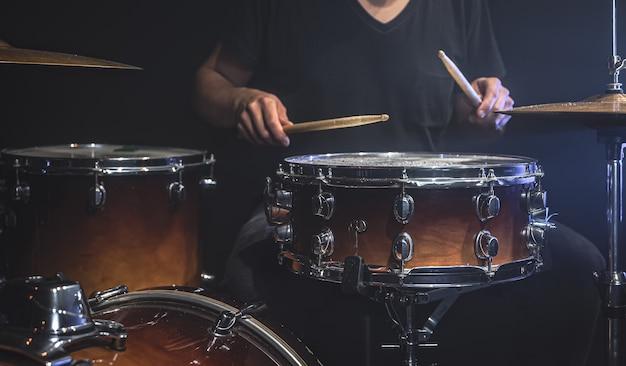 黒のtシャツを着たミュージシャンが、ステージでスティックを使ってドラムを演奏します。