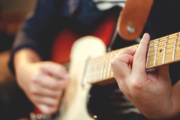 Музыкант играет на электрогитаре на концерте.