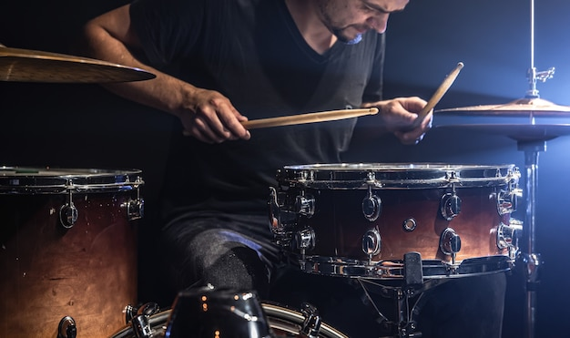 ミュージシャンは、舞台照明を備えたステージでスティックを使ってドラムを演奏します。