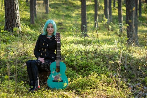 Музыкант с синими волосами и синей гитарой отдыхает в парке.