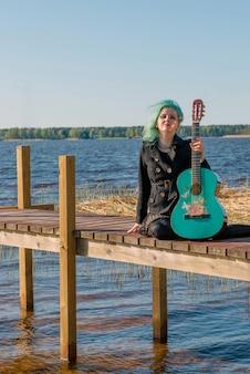 青い髪と青いギターを持つミュージシャンが湖の歩道橋に座って音楽を演奏します。