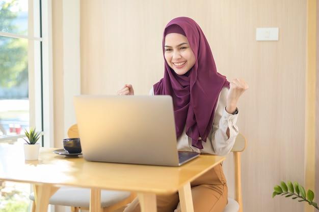 コーヒーショップで彼女のラップトップで働くヒジャーブを身に着けているイスラム教徒のビジネスウーマン
