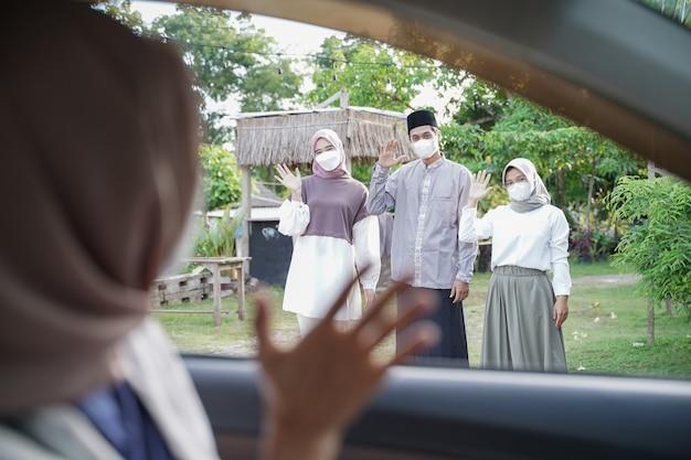 イスラム教徒の家族が車の中でスカーフで女性に手を振って立っています