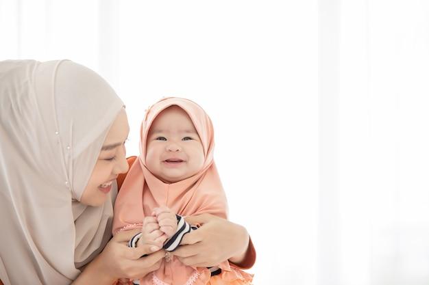 イスラム教徒の母親と幼児が寝室の屋内にいます。母親はスカーフをかぶっていて、赤ちゃんを抱っこしながらベッドに座っていて、二人とも笑顔です。
