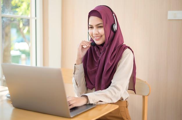 사무실에서 고객 전화에 응답하는 컴퓨터를 사용하는 헤드셋의 이슬람 운영자 여자, 고객 서비스 개념