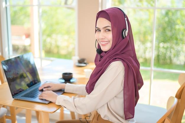 Женщина-мусульманин-оператор в гарнитуре, использующая компьютер, отвечая на звонок клиента в офисе, концепция обслуживания клиентов