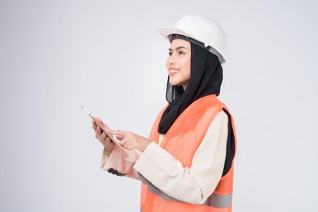 Мусульманская женщина-инженер в защитном шлеме над студией на белом фоне
