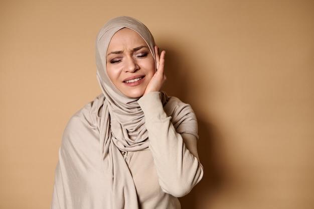 Мусульманка в строгом официальном традиционном платье с покрытой хиджабом головой страдает от зубной боли.
