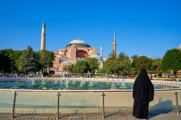 분수 옆 광장에있는 소피아 모스크를보고있는 히잡의 무슬림 여성