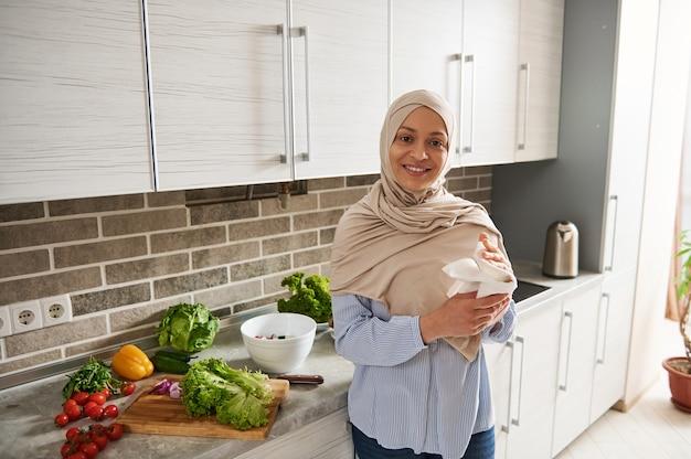 히잡을 입은 무슬림 여성이 카메라를보고 미소를 짓고 부엌에 수건을 서서 손을 닦는다.