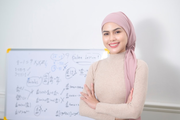 인터넷을 통해 온라인 강의를 위해 노트북을 사용하는 이슬람 여성 강사. e- 학습 및 통신 개념