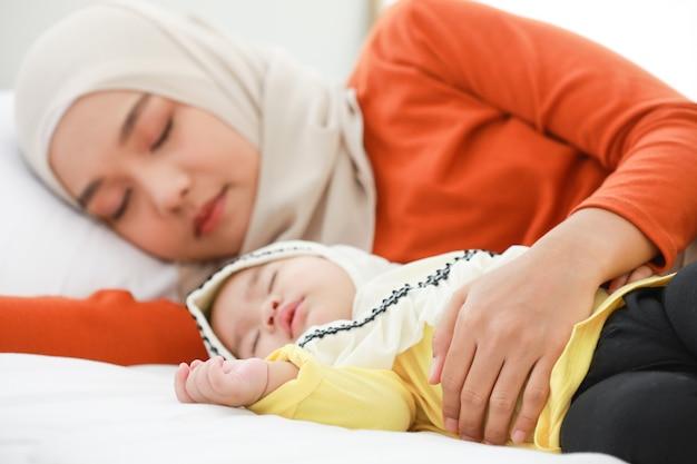ヘッドスカーフを身に着けているイスラム教徒の女性は、彼女の幼児と一緒に寝室に横たわっています。