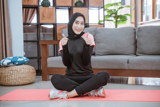 ヒジャーブのトレーニング服を着たイスラム教徒の女性が、リビングルームで親指を立てて床に足を組んで座っています Premium写真