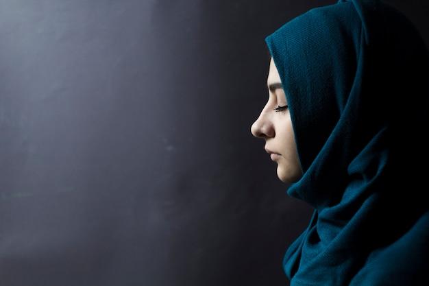 Мусульманка с закрытыми глазами, на черном фоне