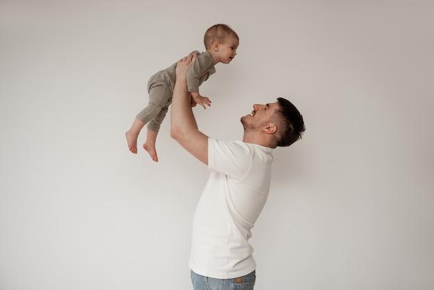 유모 남자는 작은 아기를 가지고 놀고 비행기처럼 들어 올려 아이에게 미소를 짓고 아기는 대답에 미소를 짓습니다. 흰색 배경에 밝은 색상의 사진