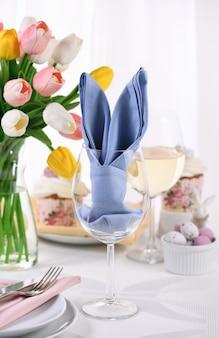 테이블을 설정하는 개념의 유리에 토끼 귀 모양으로 접힌 냅킨