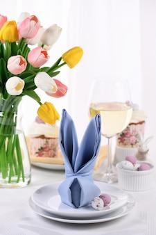 부활절의 축제 테이블을 설정하는 개념의 토끼 토끼 모양으로 접힌 냅킨