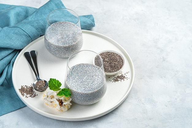 Натуральный, полезный десерт с семенами чиа и кокосовым молоком на серой стене с цветами, салфеткой и местом для копирования. вид сбоку.