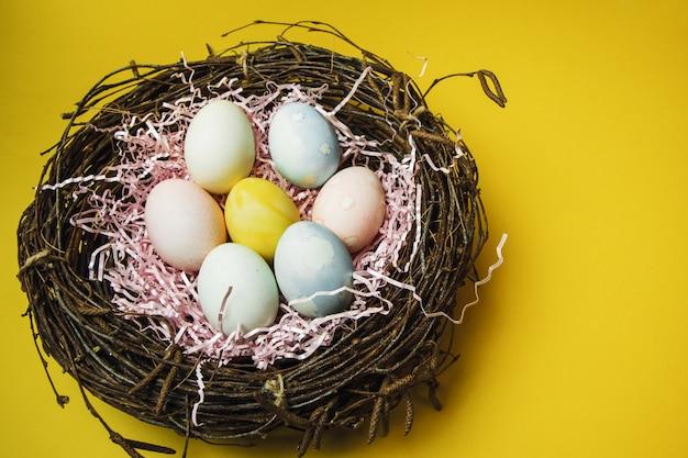 小枝と干し草の巣とパステルカラーのイースターエッグが付いたピンクの紙製フィラー。光イースターの休日のための着色された卵。黄色の背景にイースターカード
