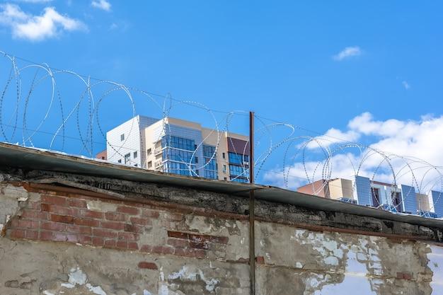 철조망이 있는 높은 벽돌 울타리 뒤에 새로운 주거 지역이 건설되고 있습니다