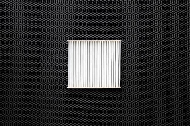 Новый квадратный белый автомобильный воздушный фильтр для кабины лежал на темном фоне