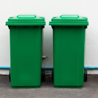 Новые большие зеленые ящики для распаковки, готовые к использованию на пешеходной дорожке и белой бетонной стене.