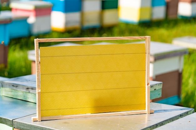 Новая деревянная рамка для пчел стоит на улье летом в саду
