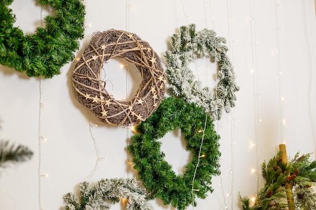 クリスマスツリーの枝からの新年の花輪が壁に掛かっています。新年の家の装飾。年末年始の部屋の飾り付け