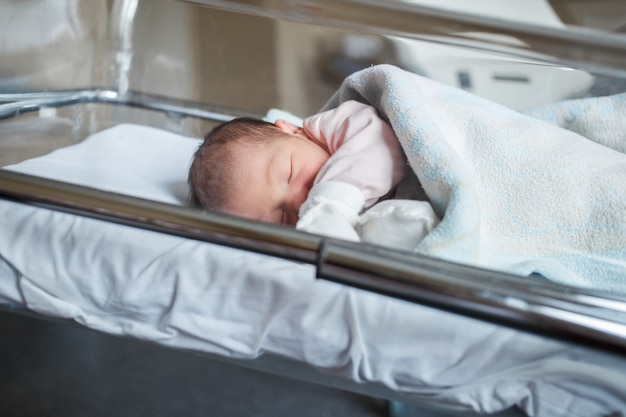 병원에있는 신생아가 상자 안에 있습니다. 작은 아기는 출생 직후 자고 있습니다.