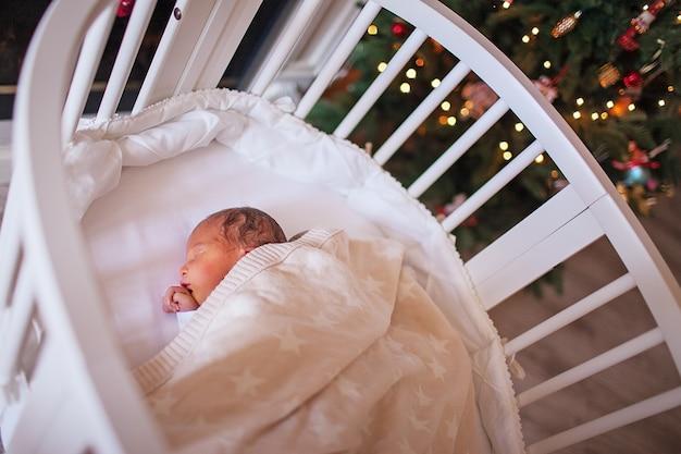 갓 태어난 아기는 크리스마스 트리를 배경으로 흰색 타원형 침대에서 잔다. 고품질 사진