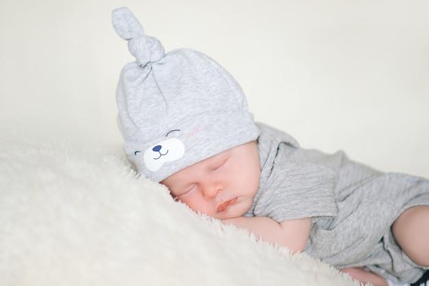 Новорожденный младенец спит лежа на животе на мягком одеяле