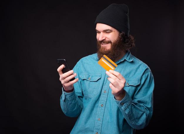 멋진 수염 난 남자가 검은 벽 근처에서 자신의 휴대 전화에서 신용 카드로 온라인 쇼핑을하고 있습니다.