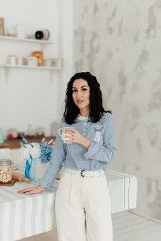 彼女の手に白いマグカップを持っている青いシャツの素敵なブルネットの女の子