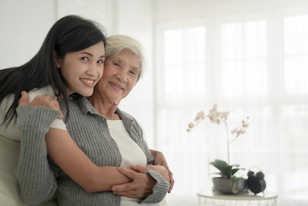 Хорошая девушка и ее бабушка наслаждаются солнечным утром. хорошо провести время дома. семья играет в гостиной