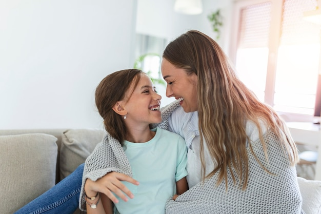 Милая девочка и ее мама наслаждаются солнечным утром. доброго времени суток дома. ребенок просыпается. семья играет под одеялом на кровати в спальне.